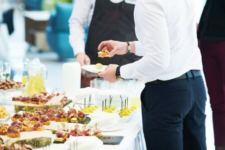 Catering service. man take snack from food court table at event