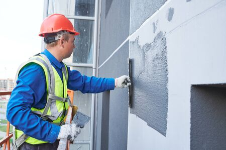 Facade worker plastering external wall of building