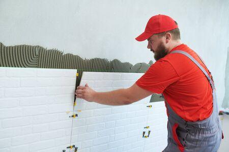 Tiler installing large size tile on wall. home indoors renovation