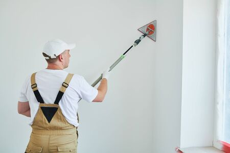 Painter work angle sander. sanding the wall corner surface after putty for painting