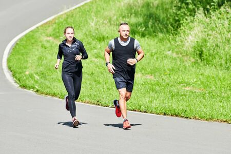 man and woman jogging and running outdoors in park Stockfoto