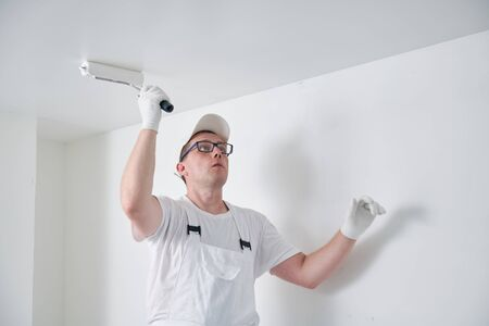 Painter worker with roller painting ceiling surface into white