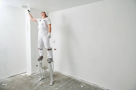 Painter worker on stilts with roller painting ceiling into white