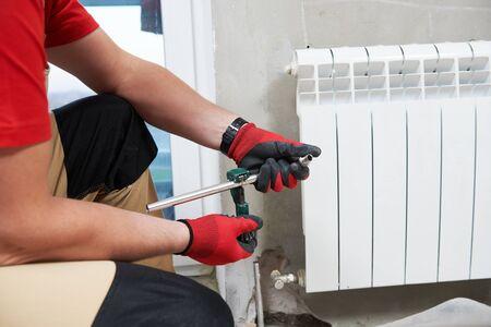 plumber at work. Installing water heating radiator Stockfoto