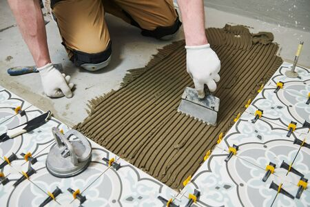 Tiler installing tile on bathroom floor. home indoors renovation Stockfoto