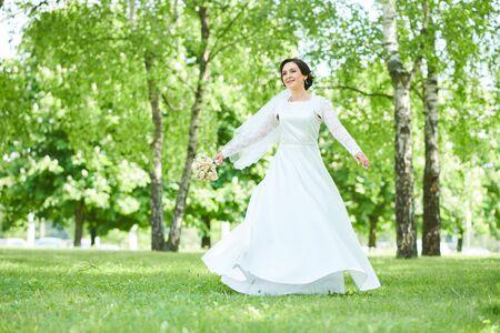 bride in wedding dress dancing in park