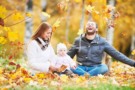 Portrait of happy young family with baby girl in autumn park