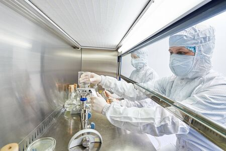 science workers in protective uniform at laboratory research work
