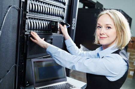 Cloud storage service. female engineer replacing hard drive in server Stockfoto