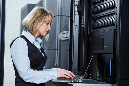 Cloud storage service. female engineer works with laptop in data center Stockfoto
