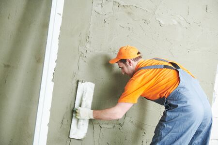 Renovation at home. Plasterer smoothing plaster on wall. Stockfoto