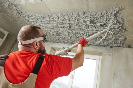 Plasterer using sprayer machine putting plaster mortar on ceiling Standard-Bild - 127286583