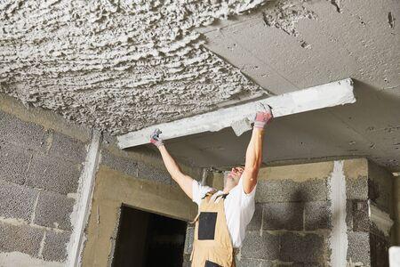 Plasterer smoothing plaster mortar on ceiling with screeder Stockfoto