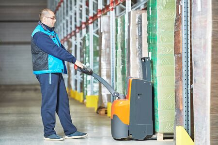 Worker with pallet truck stacking cardboxes