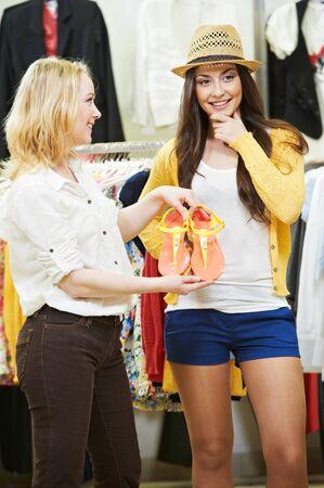 summer footwear shopping. Sale assistant demonstrates pair of Flip-flops Stockfoto