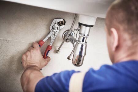 servizio idraulico. installazione del sifone della trappola del lavandino