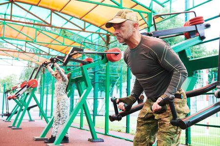 El hombre y la mujer en la formación de ropa militar al aire libre en la máquina de pesas