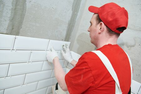 Tiler installing metro tile on wall. home indoors renovation