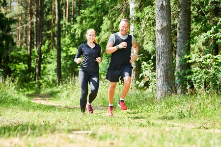 man and woman jogging and running outdoors in forest