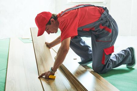 worker laying laminate floor covering at home renovation