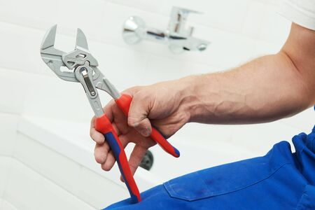 plumber service. hand with wrench in front of bathroom tap
