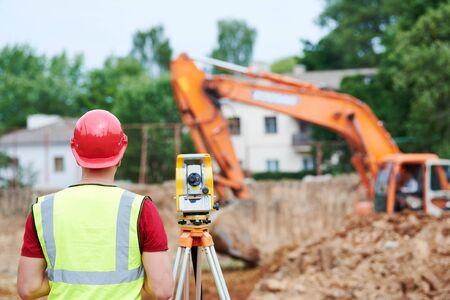 Trabajador topógrafo con teodolito en sitio en construcción Foto de archivo