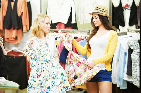 sele assistant and female buyer choosing dress in clothing shop Фото со стока - 131857392
