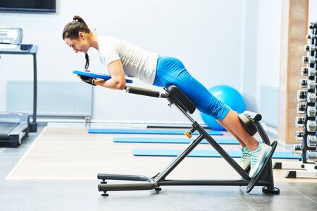 personall trainer work in gym. hyperextension exercise