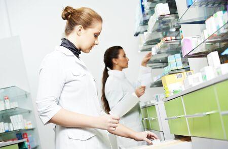 Two female pharmacutical chemists work at drugstore
