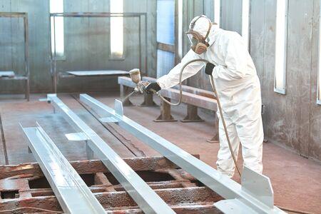 malarz przemysłowy w komorze malującej detale metalowe Zdjęcie Seryjne