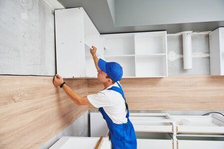 pose de cuisine. Ouvrier assemblant des meubles