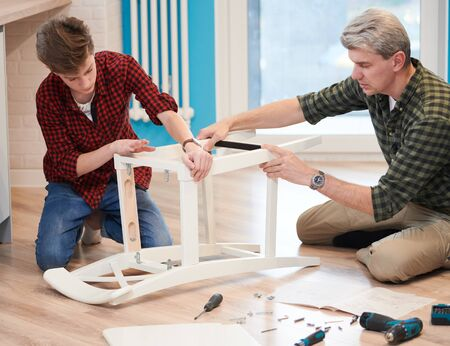 father and son work together. kitchen chair assembling