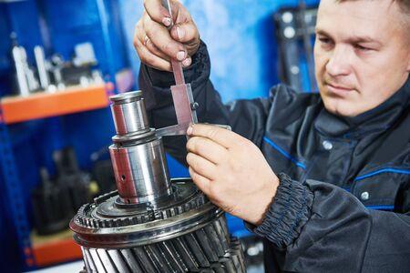Truck repair service. serviceman measuring gear shaft of gearbox