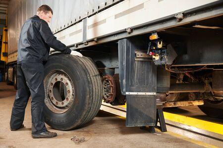 Reparatieservice voor vrachtwagens. Monteur werkt met band in vrachtwagenwerkplaats
