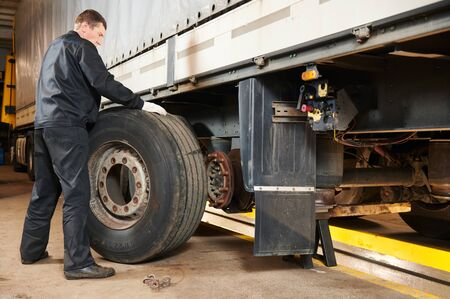 Truck repair service. Mechanic works with tire in truck workshop Imagens