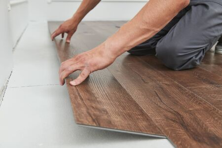 worker joining vinyl floor covering at home renovation Imagens