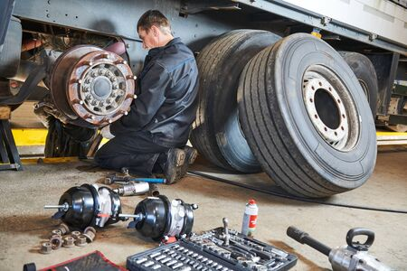 Truck repair service. Mechanic works with brakes in truck workshop Stock Photo
