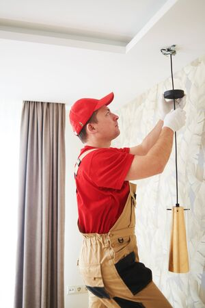 electrician works with ceiling lamp. installing or repair service