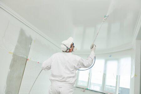 Imbianchino con spruzzatore per verniciatura airless che copre la superficie del soffitto in bianco