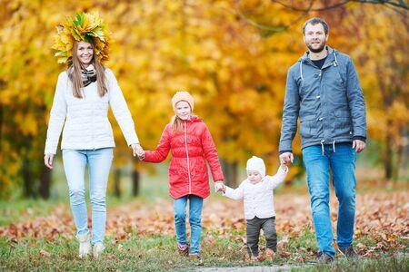 Retrato de familia joven feliz con niña en el parque otoño