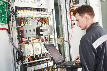 L'électricien travaille avec l'ordinateur portable dans la boîte de commutation