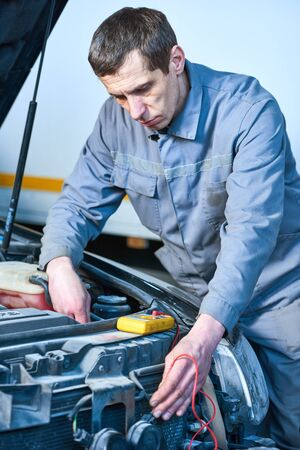 auto electrician mechanic at work with tester