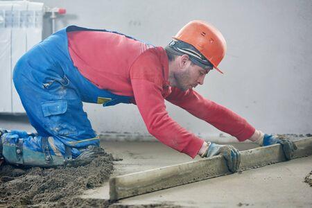 worker screeding indoor cement floor with screed Imagens