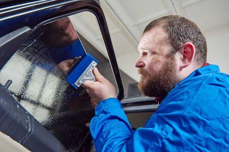 car tinting. Automobile mechanic technician applying foil Reklamní fotografie