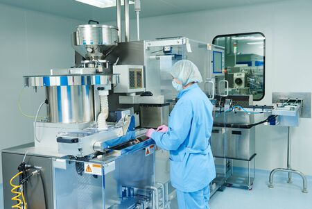 Pharmaceutics. Pharmaceutical industry worker operates blister packaging machine at factory