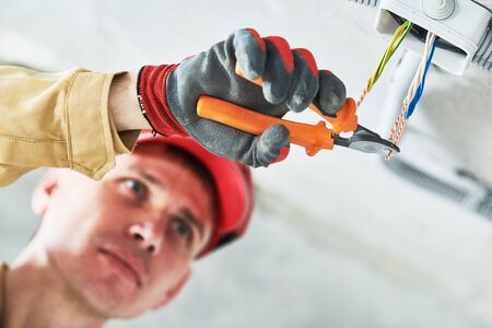 electrician service. Installer works with cable in junction box