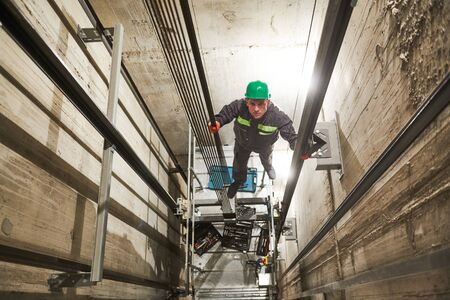 Levante el maquinista de reparación del ascensor en el hueco del ascensor