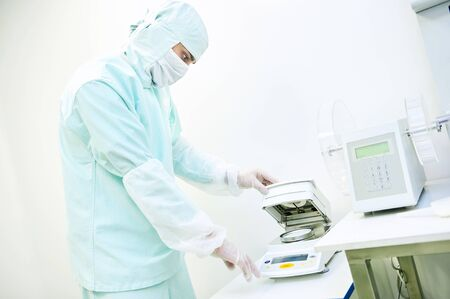 Pharmaceutical staff male worker in protective uniform working with moisture analyzer at pharmacy industry manufacture factory laboratory