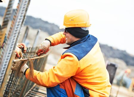 builder worker knitting metal rods bars into framework reinforcement for concrete pouring at construction site Standard-Bild