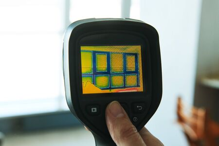 thermal imaging camera inspection of living room to check temperature leak and finding heating loss through window Standard-Bild